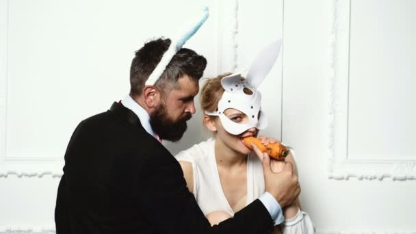 Bearded man in a suit feed woman by carrot who is dressed in a leather mask on white background. Fashion concept.