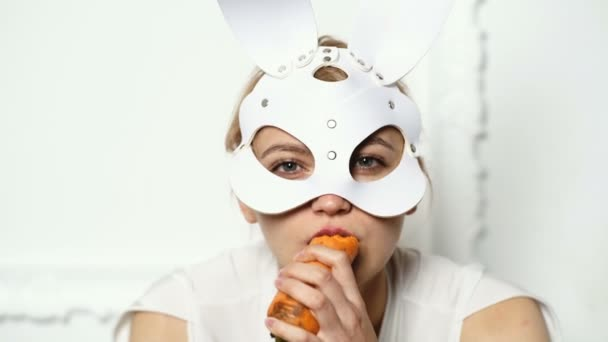 Close up of a woman in a leather mask who eats carrots. Fashion concept. BDSM concept. Hot girl in leather mask.
