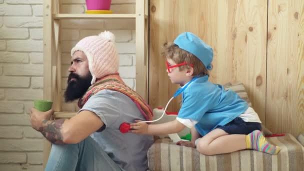 Glückliches gesundes Kind wird von einem Arzt gespielt. Arzt und Patient. Junge, gekleidet in einen Arzt hört ein Patient mit einem Stethoskop