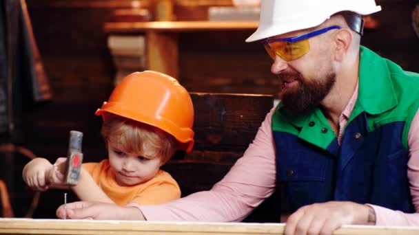 Father and son in protective helmets hammer a nail into a board. Father teaches his son a building affair.