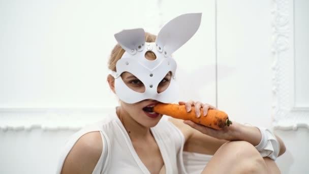 Mädchen in einer Ledermaske essen Karotten auf einem weißen Hintergrund. Leidenschaftliche Frau in einer Ledermaske. Hot Girl mit dicken Karotten in ihrer hand.