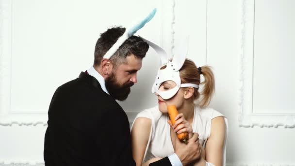Bearded man with rabbit ears feeding a woman by carrot in a leather mask. BDSM concept. Passionate couple with rabbit ears on a white background.