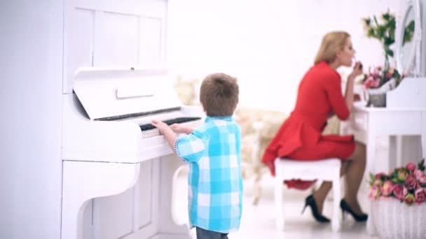 A fiú játszik a zongora, míg anyja egy smink teszi, fésülködő asztal. A kisfiú játszik a zongora egy fehér szobában a háttérben, az anyja, aki a smink. Fiú játszik a zongora.