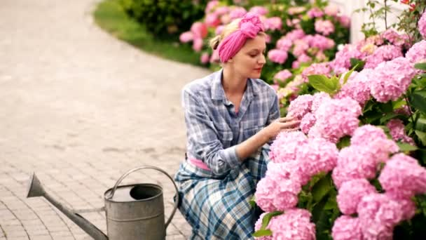 Girl with a pink ribbon on her head cares for flowers. Woman with a watering can cultivates flowers in the garden. Spring concept, nature and care.