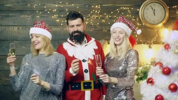 Szakállas férfi egy új év jelmez és két lány piros sapka, égő lámpák bengáli és pezsgőt isznak. Új év party. Új év hangulat fogalmának. Férfi és két lány találkozik új év.