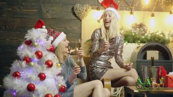 Csinos lányok pezsgőt igyon és éget bengáli fények mellett a karácsonyfa. Vicces lány: új év party. A szilveszteri hangulat fogalmának. Új év alapon a ragyogó ruhák lányok.