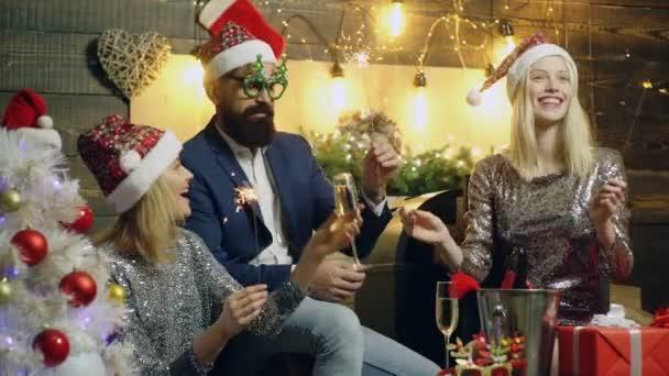 Nový rok party u vás doma. Muž a dvě dívky slaví Vánoce, pili šampaňské a hořící jiskru světla. Koncept nového roku a vánoční náladu.