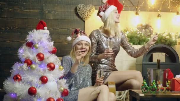 Két lány ivott pezsgőt és éget bengáli fények, háttérben az új év táj ragyogó ruhák viselése. Két lány ünneplik az új évet. Fogalmának ünneplő karácsony.