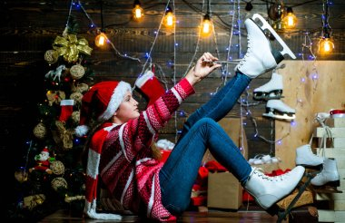White Skates. Christmas Xmas winter holiday concept. Cute little teenager celebrating Christmas. Funny kid holding Christmas gift. Celebration holiday.