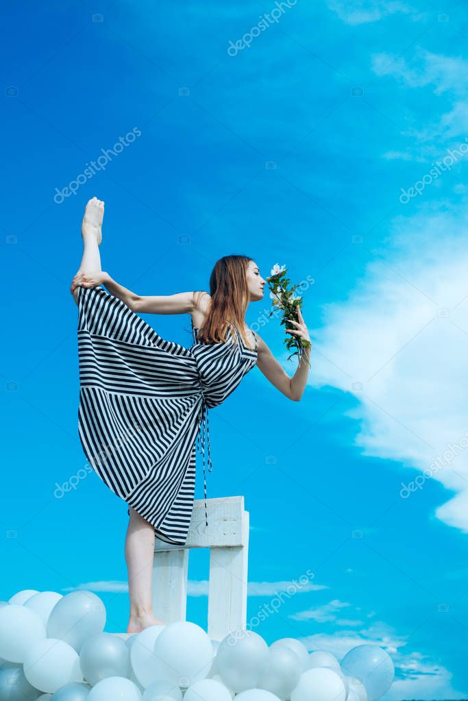 Fashion portrait of woman. girl with flowers sit in sky. feeling freedom and dreaming. inspiration and imagination. woman in summer dress with party balloons. acrobatics and sport. spli