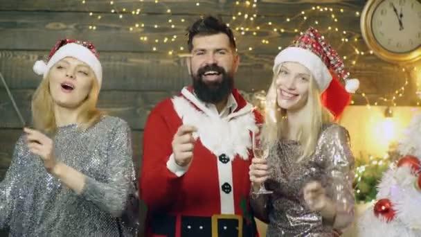 Bärtiger Mann in Santas Kostüm und zwei Prety Mädchen in neuen Jahren Hüte Wunderkerze Lichter brennen und trinken Champagner auf dem Hintergrund des neuen Jahres. Silvester-Party. Neujahr-Mood-Konzept.