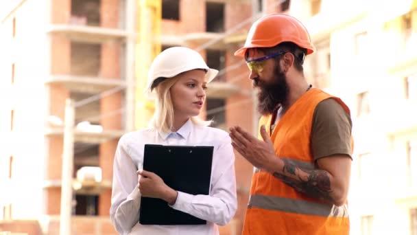 Žena v ochrannou přilbu komunikuje s tvůrce v přilbu a ochrannou vestu na staveništi. Koncepce plánování etap výstavby