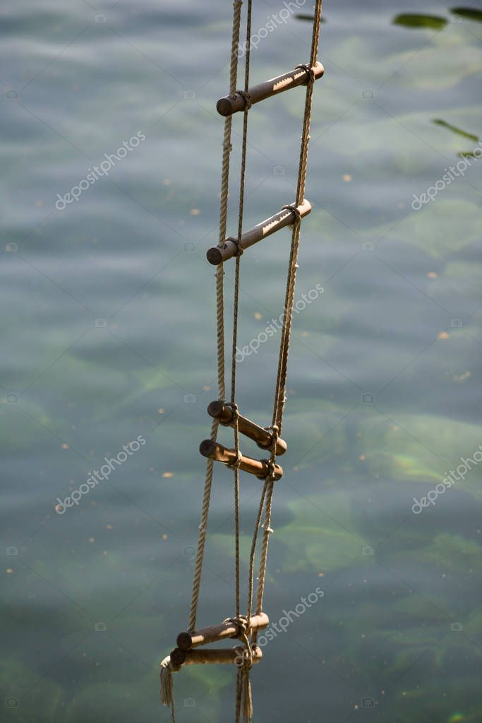 Achieving success. Rope ladder. Jacobs ladder. Rope ladder with wooden steps. Rope over water surface. Rescue or escape rope. Climbing the ladder of success. Height of ambition