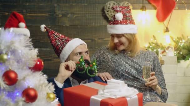 Lány egy új év hat szakállas ember, aki egy nagy piros négyzet ajándékok a háttérben Szilveszter táj közelében ült. Szilveszteri hangulat, a előestéjén az újévi ünnepek