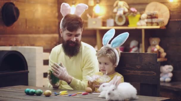 Father and son color the Easter eggs. Cute little child boy wearing bunny ears. Easter eggs on wooden background. Happy easter.