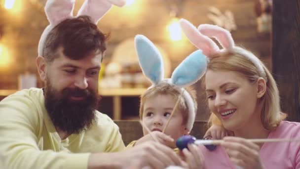 Father, mother and kid boy painting Easter eggs. Happy family are preparing for Easter. Cute little child boy wearing bunny ears. Easter eggs on wooden background.