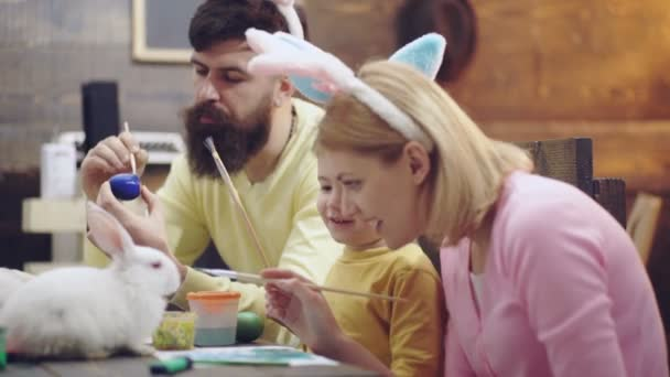 Mother, father and son are painting eggs. Happy family are preparing for Easter. Cute little child boy wearing bunny ears. Happy easter. Easter bunny. Easter eggs on wooden background.