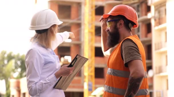 Discuss progress project. Inspector and bearded brutal builder discuss construction progress. Construction project inspecting. Construction inspection, corrections and fines. Safety inspector concept.