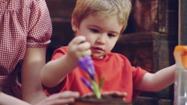 Zblízka se chlapec zahradníka, který zasadit květiny v květináčích. Máma a syn se zabývají zahradnictví, pěstování květin v barevných hrnce. Koncept zahradnictví