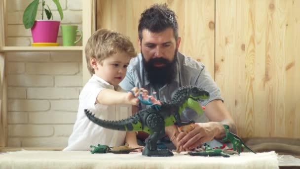 Malý chlapec s tátou. Šťastné dětství. Péče a rozvoj. Otec s dětskou konstruktorem. Šťastné rodinné a dětské dny. Malý chlapec hraje doma s rodiči. Rodinný den.
