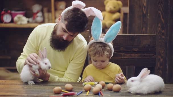 Boldog család készül a húsvét. Aranyos kis gyermek fiú nyuszi füle visel. Férfi és fiú festett húsvéti tojás fa háttér.
