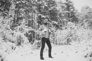 Bearded man with skates in snowy forest.
