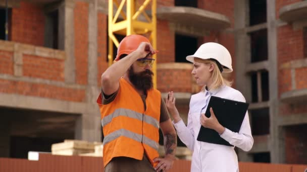 4K Engineers at construction site looking at plans and discussing the project. Two young engineers man and female have a discussion on the construction site. Builders on construction.