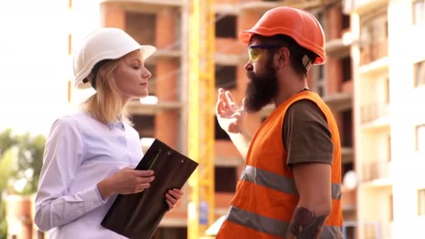 Male and female civil engineers talking on a construction site. male and female builders in construction.