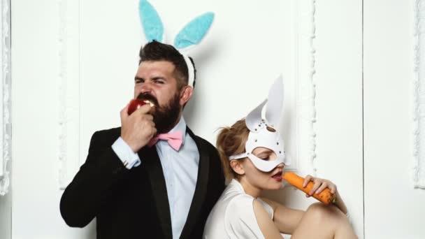 Paar in Hase Kostüme mit Karotten und Apfel. Sexy Hase paar auf weißem Hintergrund. Pin-up Frau Vintagelook. Retro-Frau in Hasenohren, Ostern. Schönheit, Mode, Kosmetik, Vintage-Stil.
