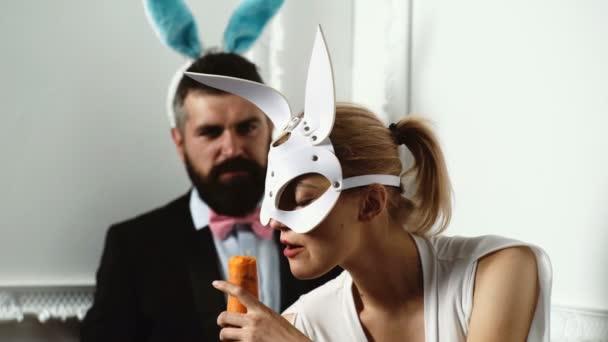 Heiße sexy Ostern-paar mit Hasenohren. Nahaufnahme eines Mädchens in einer Ledermaske Kaninchen, Karotten vor dem Hintergrund eines bärtigen Mann isst die Hasenohren trägt. Schöne Sexy Bunny Girl.