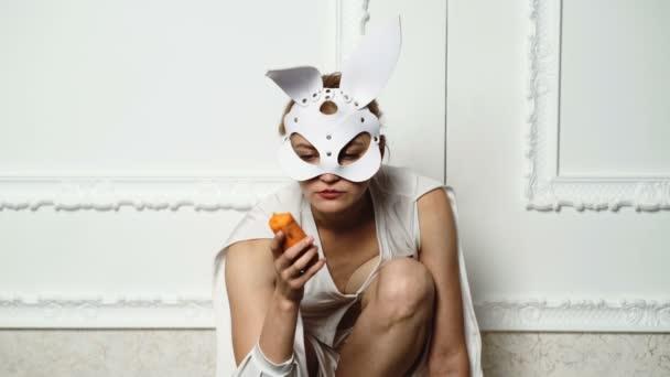 Beautiful Sexy Bunny Girl. Junge Frau in Bunny Ledermaske essen Karotten auf weißen Vintage-Hintergrund. Sexy Ostern Osterhase Mädchen.
