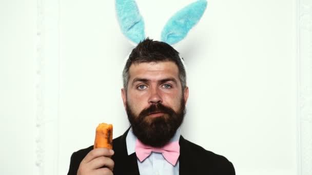 Osterhase Junge isoliert auf weißem Hintergrund. bärtiger Mann in Hasenohren isst Karotte auf weißem Hintergrund. Frohe Ostern. Modemann. Hipster-Mann mit Hasenohren.