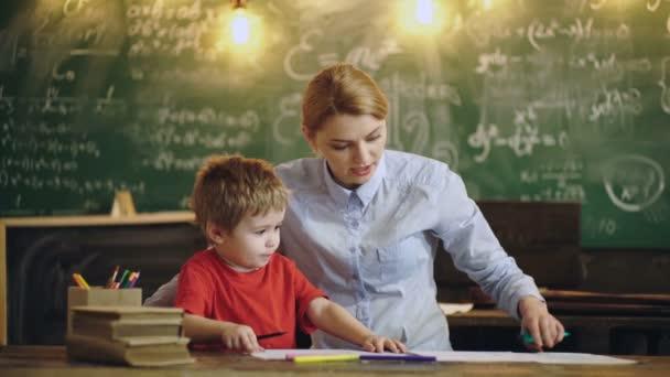Učitel pro výuku školák v učebně ve škole. Učitel v učebně. 4 děti základní školy k výkresu v učebně s učitelem pomáhá.