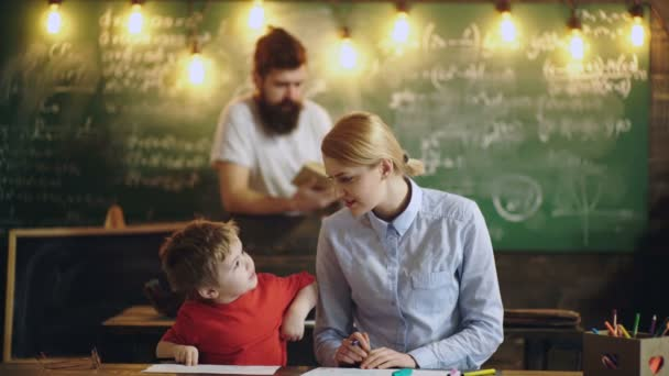 Teacher and little boy draw and talk on the background of a green board and bearded professor. Back to school background with books and profesor over blackboard. Learning concept.
