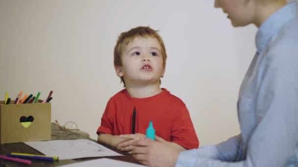 Junge zeichnet mit einem Lehrer isoliert auf weißem Hintergrund. Lehrer im Klassenzimmer. 4k Grundschulkinder malen im Klassenzimmer mit Hilfe des Lehrers. Lehrer und Schüler. Zurück zur Schule.