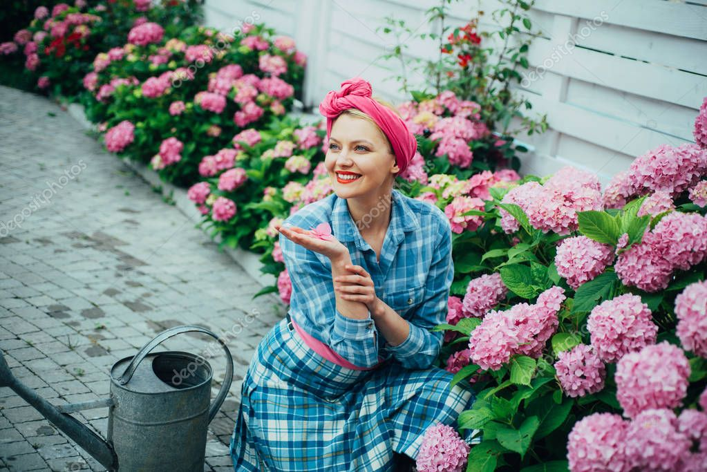 Flower care and watering. soils and fertilizers. happy woman gardener with flowers. woman care of flowers in garden. Greenhouse flowers. hydrangea. Spring and summer. I love gardening
