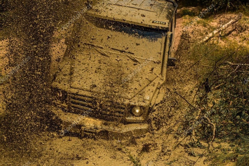 Mud and water splash in off-road racing. Expedition offroader. Best Off Road Vehicles. Offroad vehicle coming out of a mud hole hazard. Tracks on a muddy field.