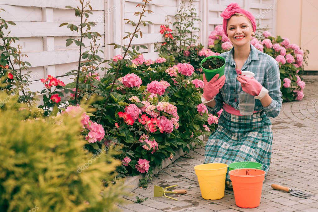 woman care of flowers in garden. happy woman gardener with flowers. hydrangea. Spring and summer. Greenhouse flowers. Flower care and watering. soils and fertilizers. She love working with flowers