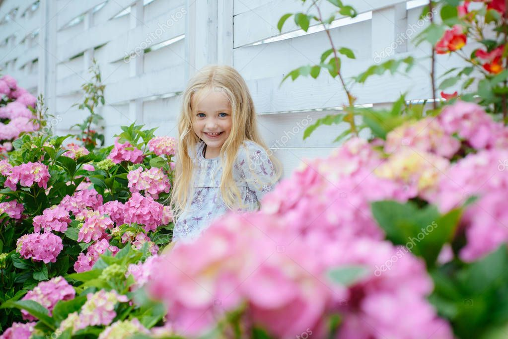 Summer. Mothers or womens day. Little girl at blooming flower. Childrens day. Small baby girl. Spring flowers. Childhood. New life concept. Spring holiday. happy girl. Hot summer