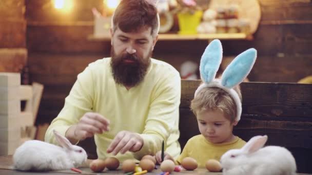 Otec a syn malovat velikonoční vajíčka. Velikonoční svátky. Šťastná rodina, příprava na Velikonoce. Veselé velikonoce. Velikonoční vajíčka. Velikonoční vajíčka na dřevěné pozadí.