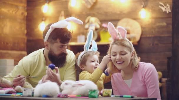 Matka, otec a jejich děti chlapec malování vajíček. Šťastná rodina, příprava na Velikonoce. Velikonoční vajíčka. Na sobě uši zajíček o Velikonocích roztomilý chlapeček dítě. Krásné dítě chlapec malování kraslic.