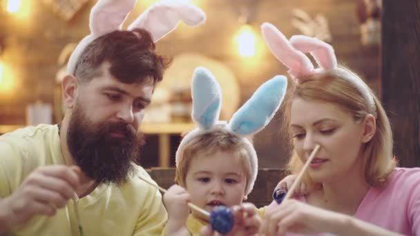 Detail šťastné rodiny, které jsou malování kraslic. Na sobě uši zajíček roztomilý chlapeček dítě. matka, otec a jejich syn, malování kraslic. Velikonoční vajíčka na dřevěné pozadí.