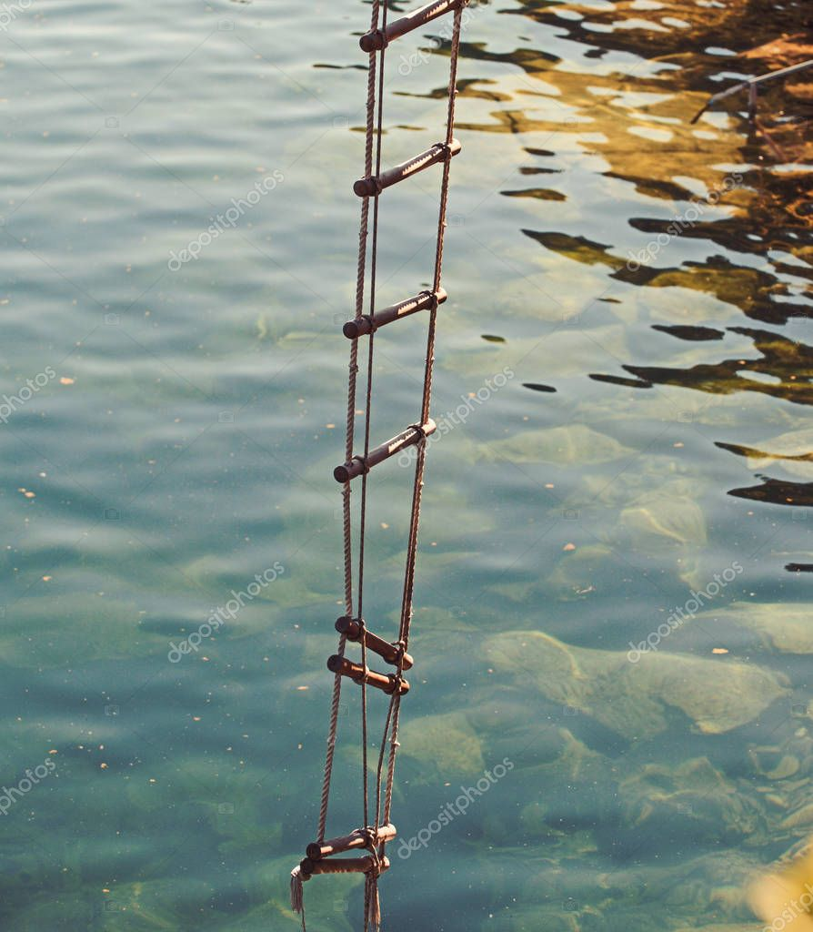 The ladder of success is never crowded at the top. Rope ladder with wooden steps. Rope over water surface. Rescue or escape rope. Jacobs ladder. Height of ambition. Ambition is the path to success
