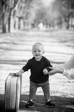 Child travel for vacation with bag with mothers hand. Small boy carry retro suitcase on natural landscape. Kid traveler with luggage outdoor. Vacation traveling and wanderlust
