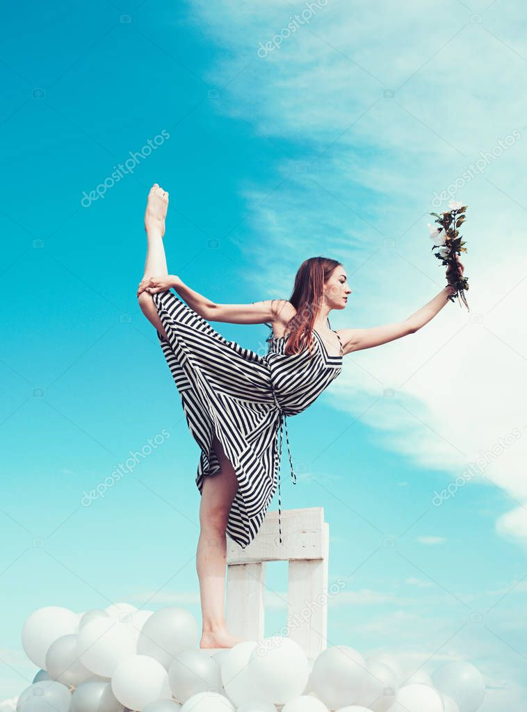 woman in summer dress with party balloons. girl with flowers sit in sky. feeling freedom and dream. inspiration imagination. Fashion portrait of woman. split. dancing in the sky. sport and success