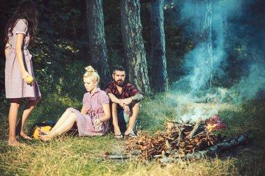 Kadın ve erkek, vintage tarzı kampında yangın. Arkadaşlar kamp ateşi sakin ol. Şenlik ateşi insanlara yeşil ormanda alev. Kamp, yürüyüş ve turistik. Yaz tatil kavramı