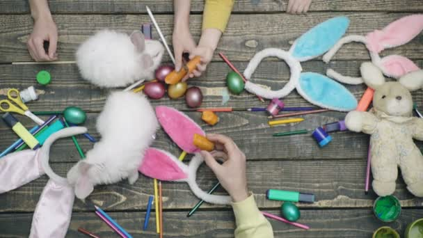Top view of the hands that paints Easter eggs and feed Easter hare with carrots. Happy family are preparing for Easter. Easter eggs on wooden background.