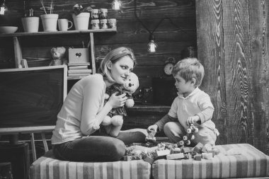 Kindness and education concept. Family play with teddy bear at home. Mom and child play with soft toy. Nursery with chalkboard on background. Mother teaches son to be kind and friendly.