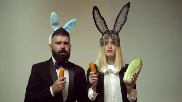 Funny easter bunny. Happy funny easter couple with carrot. Family celebrate Easter. Easter rabbits. Couple with bunny ears.