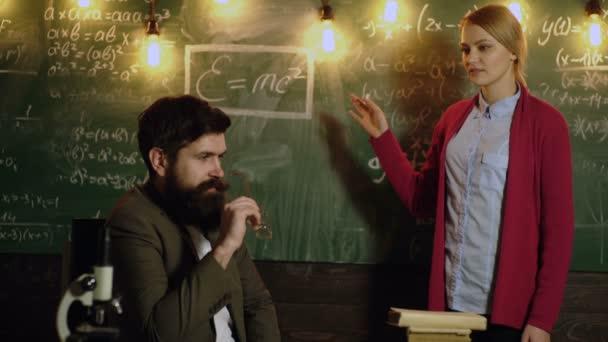 Akadémiai férfi és a nő matematikai képletek írni a táblára, és megvitathatják elképzeléseiket. Tanárnő az osztályban. Tanár és diák. Tanulás-fogalom. Osztálytársa nevelés barátom tudás lecke koncepció.